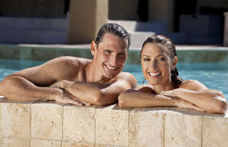 Close up portrait of a beautiful happy man and woman couple resting on their hands at the side of a sun bathed swimming pool smiling with perfect teeth. photo