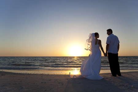 Hochzeit ein verheiratetes Paar, Braut und Bräutigam, bei Sonnenuntergang an einem wunderschönen tropischen Strand zusammen