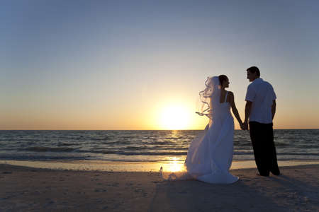 Wedding of a married couple, bride and groom, together at sunset on a beautiful tropical beach Stock Photo