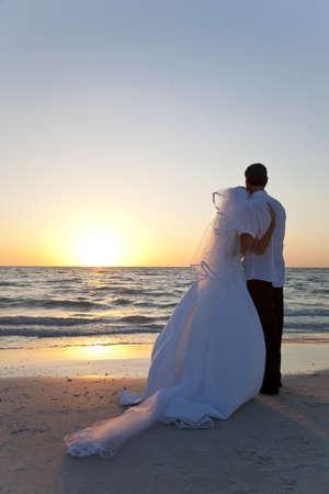 luna de miel: Boda de una pareja casada, la novia y el novio, junto al atardecer en una hermosa playa tropical