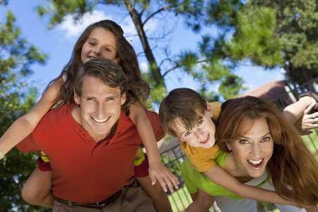 An attractive happy, smiling family of mother, father, son and daughter having fun outside in a park in warm summer sunshine Stock Photo - 8806843