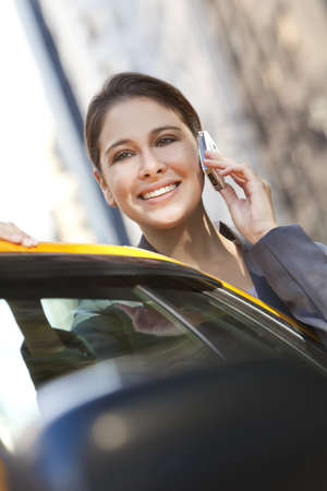 A happy young woman talking on her mobile cell phone getting into the back of a yellow taxi cab. Shot on location in New York City Stock Photo - 8806905