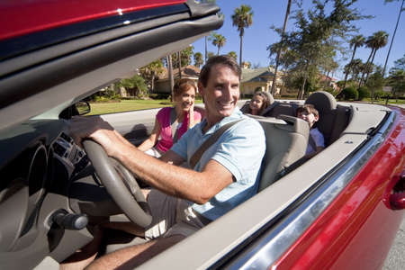 Man and woman parents and two children having fun driving in a red convertible car in sunshine photo