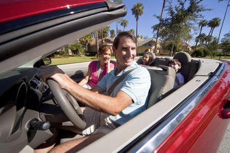 rijke vrouw: Ouders van man en vrouw en twee kinderen plezier rijden in een rode converteerbare auto in zon