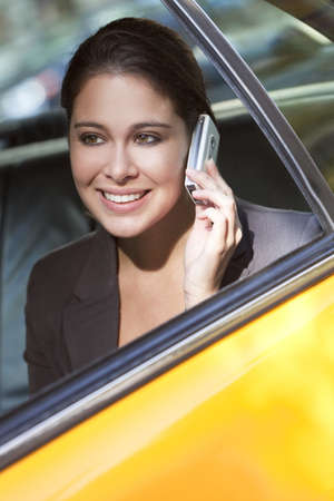 location shot: A happy young woman talking on her mobile cell phone in the back of a yellow taxi cab. Shot on location in New York City Stock Photo