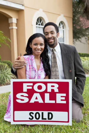 A happy African American man and woman couple outside a large house with a For Sale Sold sign celebrating the purchase of a property photo