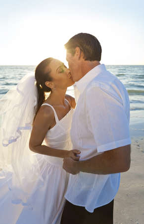 Married couple, bride and groom, kissing at sunset on a beautiful tropical beach wedding photo