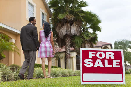look for: A happy African American man and woman couple house hunting outside a large house with a For Sale sign. The focus is on the sign.