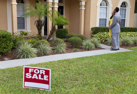 front of house: A happy African American man and woman couple house hunting outside a large house with a For Sale sign