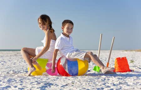 beach ball girl: Los ni�os peque�os, ni�o y ni�a, hermano y hermana, divertirse, jugando en una playa con pelotas de playa, baldes y picas Foto de archivo