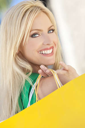 Natural light portrait of a happy beautiful blond woman with blue eyes carrying shopping bags Stock Photo - 8806923