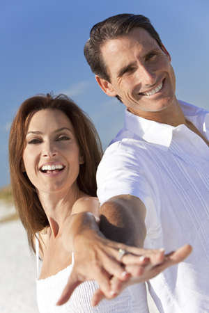 Attractive middle aged man and woman romantic couple in white clothes holding hands to camera on a tropical beach with bright clear blue sky photo