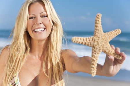 A beautiful young blond woman holding a starfish wearing a bikini on a beach and laughing photo