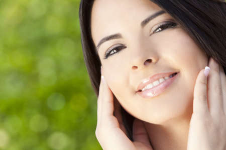 Outdoor portrait of a beautiful young Latina Hispanic woman hands on her face and with natural green background Stock Photo - 8955225