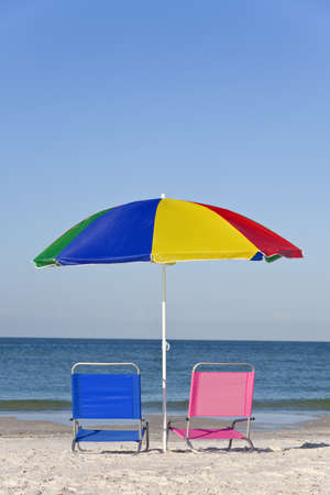 Pink and blue deck chairs on a beach underneath a colourful umbrella or parasol photo
