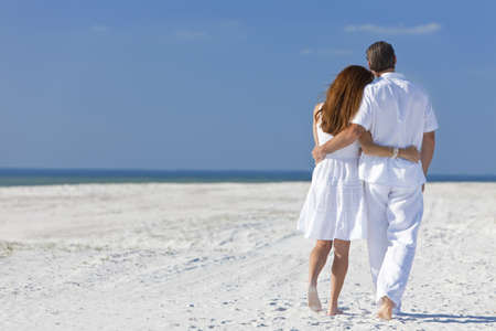 Rear view of man and woman romantic couple in white clothes walking on a deserted tropical beach with bright clear blue sky photo