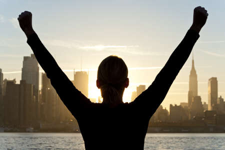 Rear view silhouette of a woman celebrating arms raised at sunrise in front of the Manhattan skyline New York City, United States of America photo