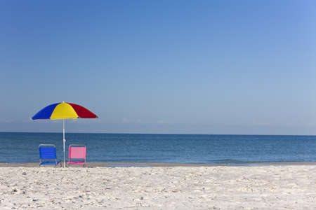 Pink and blue deck chairs on a beach underneath a colourful umbrella or parasol Stock Photo