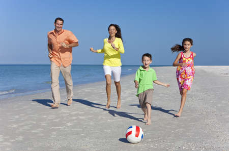 A happy family of mother, father and two children, son and daughter, running kicking a football and having fun in the sand of a sunny beach Stock Photo
