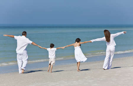 Rear view of a happy family of mother, father and two children, son and daughter, running holding hands and having fun in the sand of a sunny beach