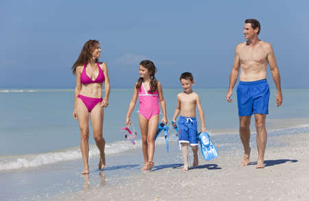 swimming costumes: A happy family of mother, father and two children, son and daughter, in swimming costumes having fun in the sea on a sunny beach