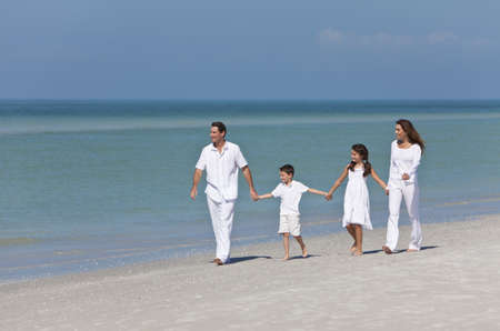 A happy family of mother, father and two children, son and daughter, walking and holding hands on a sunny tropical beach photo