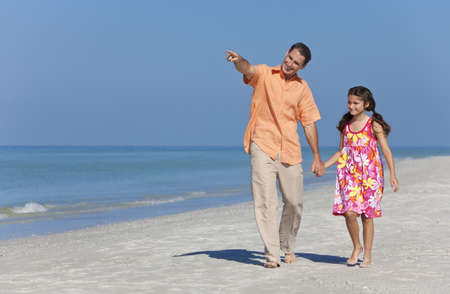 A happy father and child, his daughter, walking holding hands and pointing on a sunny beach photo