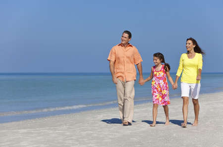 A happy family of mother, father and daughter, holding hands and walking in the sand of a sunny beach photo