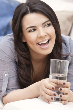 Portrait of a beautiful young Latina Hispanic woman laying down on a sofa, laughing and drinking a glass of water photo
