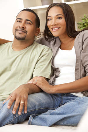 A happy African American man and woman couple in their thirties sitting at home Stock Photo - 9150648