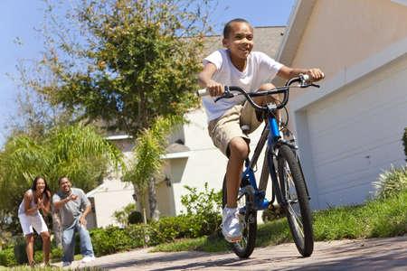 ni�os en bicicleta: Una joven familia afroamericana con ni�o chico montar su bicicleta y sus padres emocionados felices dando aliento detr�s de �l Foto de archivo