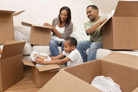 瀬戸物: アフリカ系アメリカ人の家族、両親と息子、ボックスを開梱し、大人をアンパックしている食器と家庭用品、新しい家に移動、子供はおもちゃの飛行機をアンパックします。