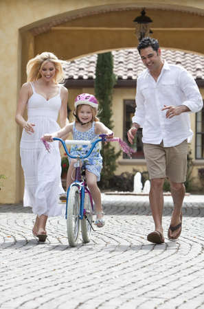 A young family with girl child riding a bicycle and her happy excited parents giving encouragement and running alongside her photo