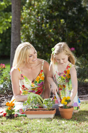 family gardening: Woman and girl, mother and daughter, gardening together planting flowers and tomato plants in the garden