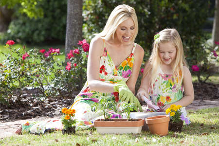 Woman and girl, mother and daughter, gardening together planting flowers and tomato plants in the garden Stock Photo - 9150682