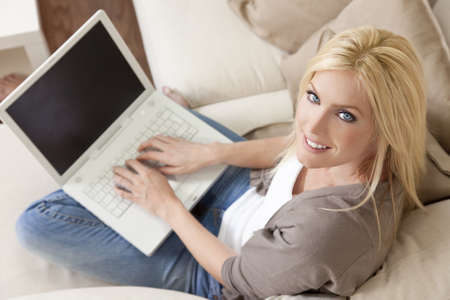 Overhead photograph of beautiful young woman at home sitting on sofa or settee using her laptop computer and smiling photo