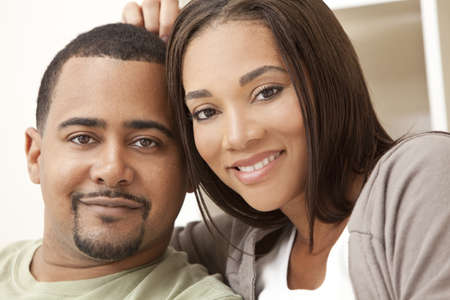 human relationship: A happy African American man and woman couple in their thirties sitting at home Stock Photo