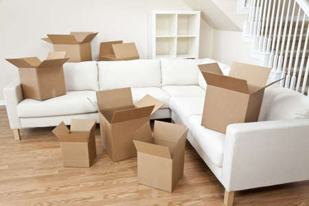 settee: Empty room full of cardboard boxes for moving into a new home.