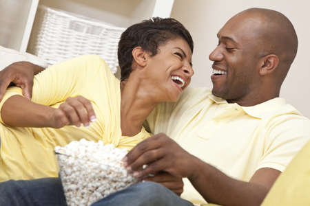 laughing couple: A happy African American man and woman couple in their thirties sitting at home laughing, eating popcorn and watching a movie together Stock Photo