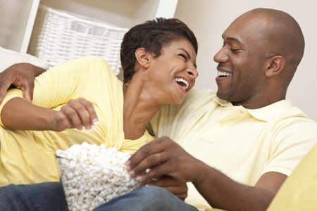 esposas: Una feliz pareja hombre y mujer afroamericana en sus treinta a�os sentado en casa riendo, comiendo palomitas de ma�z y viendo una pel�cula juntos