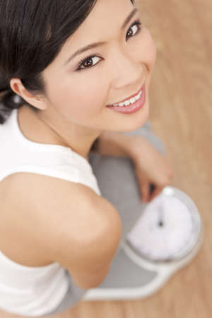 Over head view of happy & beautiful Oriental Asian Chinese woman weighing herself on scales at gym or health club Stock Photo - 9150700