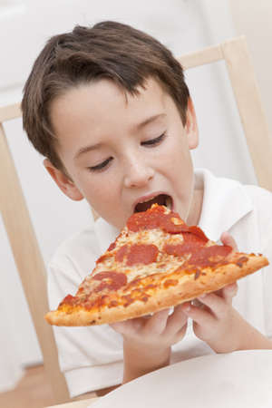A young boy child eating a slice of pepperoni and cheese pizza photo