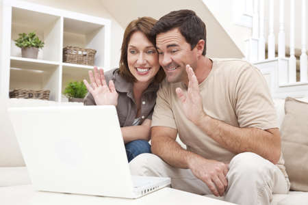 Happy man and woman couple in their thirties, sitting together at home on a sofa using a laptop computer to make a VOIP internet phone call and waving at the screen photo