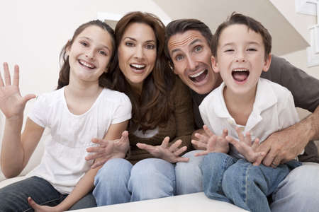 people laughing: An attractive happy, laughing family of mother, father, son and daughter sitting on a sofa at home having fun