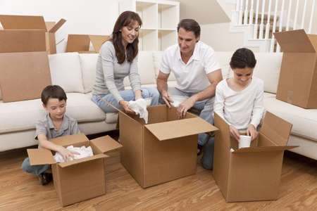 unpacking: Family, parents, son and daughter, unpacking boxes and moving into a new home. Stock Photo