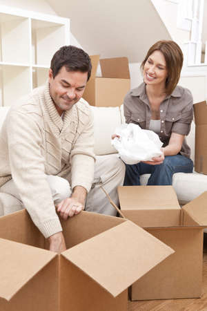 Happy couple in their thirties unpacking or packing boxes and moving into a new home. photo