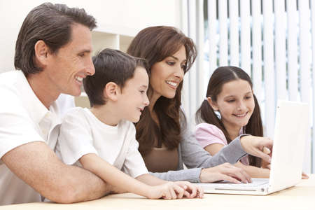 An attractive happy, smiling family of mother, father, son and daughter sitting at a table using a white laptop computer photo