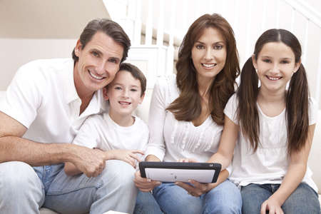 Una familia feliz, atractiva de la madre, padre, hijo y su hija sentado en un sof� en casa divirti�ndose con un tablet PC Foto de archivo - 9181515