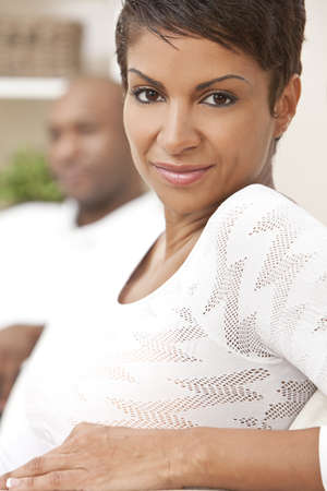 A happy African American man and woman couple in their thirties sitting at home, the woman is in focus in the foreground the man out of focus in the background. Stock Photo - 9181521