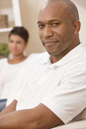 A happy African American man and woman couple in their thirties sitting at home, the man is in focus in the foreground the woman out of focus in the background. photo